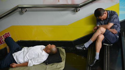 Two men take shelter from the heat in a metro station in Shanghai on Tuesday, July 2.