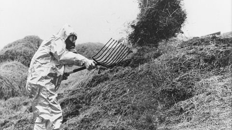 A farmer in Sweden wears anti-atomic clothes as he sifts hay possibly contaminated by the radioactive cloud from Chernobyl in June 1986.