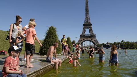 People sunbath on lawns near the Eiffel Tower in Paris, on August 1.