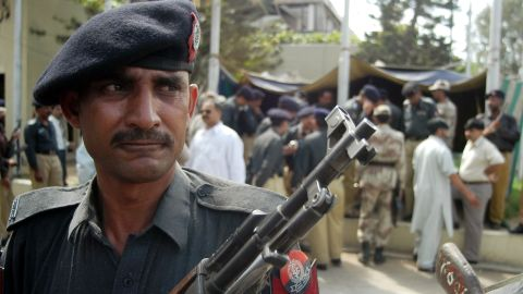 """A Pakistani police officer stands guard outside the <a href=""""http://articles.cnn.com/2003-02-28/world/karachi.shooting_1_consulate-compound-bomb-attack-karachi"""">U.S. Consulate in Karachi</a> after a gunman opened fire there on February 28, 2003. Two police officers were killed, and six others, including one civilian, were injured."""