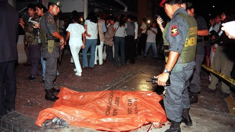 """Police officers stand next to the body of a victim after a car bomb exploded on March 20, 2002, at a shopping center near the <a href=""""http://archives.cnn.com/2002/WORLD/americas/03/21/peru.embassy.blast/"""">U.S. Embassy in Lima, Peru,</a> killing nine people."""