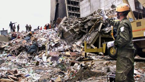 """Rescue workers stand on the remains of a building in front of the <a href=""""http://www.cnn.com/WORLD/africa/9808/08/africa.explosions.01/"""">U.S. Embassy in Nairobi, Kenya,</a> on August 10, 1998, four days after a deadly attack. Twelve Americans were among more than 200 people killed in nearly simultaneous bombings at U.S. embassies in Nairobi and Dar es Salaam, Tanzania."""