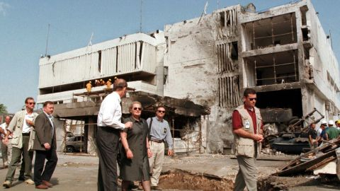 """Secretary of State Madeleine Albright, center, walks past the damaged <a href=""""http://www.cnn.com/WORLD/africa/9808/08/africa.explosions.01/"""">U.S. Embassy in Dar es Salaam</a> on August 18, 1998. The August 7 attacks in Tanzania and Kenya were later attributed to al Qaeda."""