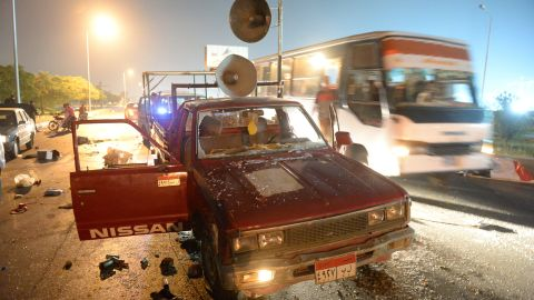 """A bus passes a destroyed pickup truck with loudspeakers that was used by supporters of ousted Egyptian President Mohamed Morsy on Friday, August 2. The supporters and security forces clashed in Sixth of October City in Giza, south of Cairo, after the government ordered their protest camps be broken up. <a href=""""http://www.cnn.com/2013/08/15/middleeast/gallery/egypt-violence-august/index.html"""" target=""""_blank"""">Look at the latest violence in Egypt.</a>"""