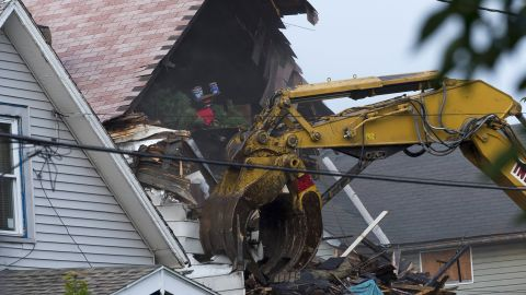A crane demolishes the Cleveland house of Castro on August 7. Plans call for the house to be torn down and the lot cleared in a single day.