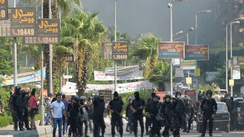 Egyptian riot police disperse supporters of Egypt's ousted president Mohamed Morsi and members of the Muslim Brotherhood as security forces crackdown on two major pro-Morsi protest camps, on August 14, 2013 near Cairo's Rabaa al-Adawiya mosque.