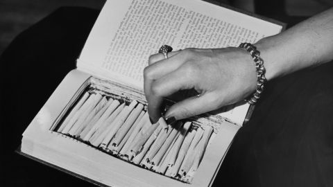Marijuana cigarettes are hidden in a book circa 1940. Congress passed the Marijuana Tax Act in 1937, effectively criminalizing the drug.