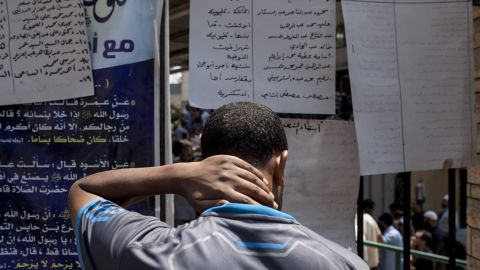A man on checks out a list of names of those killed in the crackdown on, on August 15, 2013.