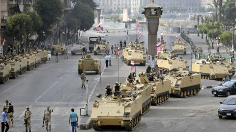 Egyptian soldiers take positions alongside armored vehicles as they guard the entrance to Tahrir Square in Cairo on Friday, August 16, 2013.