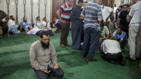 A supporter of deposed Egyptian President Mohammed Morsi prays on the floor of the Fateh Mosque at Ramses Square as an injured protesters is treated nearby on August 16, 2013 in Cairo, Egypt.