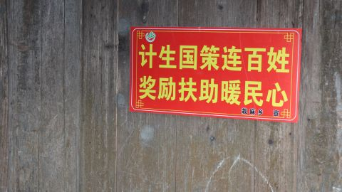"""Propaganda slogans are commonplace in Chinese villages to encourage people to comply with government policies. This one reads: State family planning policy connects everyone. Rewards and subsidies warm the heart of the people."""""""