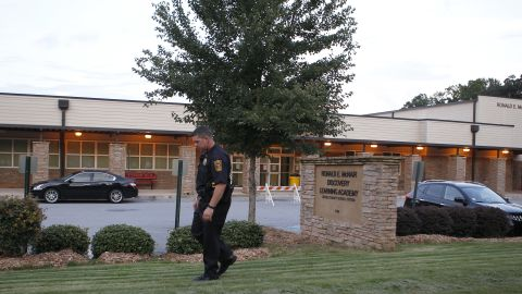 """A policeman walks in front of Ronald E. McNair Discovery Learning Academy after a shooting incident in Decatur, Georgia, on Tuesday, August 20. Michael Brandon Hill, 20, opened fire at the school armed with an AK-47 """"and a number of other weapons,"""" police said. There were no reports of injuries."""