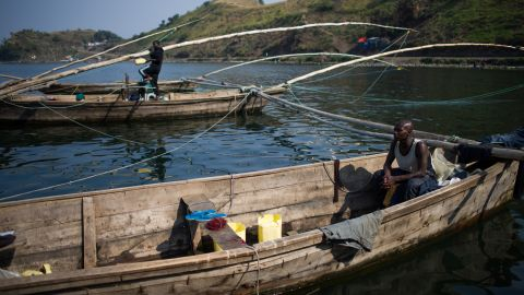 """A fisherman sits in a boat on the shore of Lake Kivu in Goma in August. """"There are no big fish because of the gas; we only catch small whitebait,"""" one said of the carbon dioxide and methane that saturate the lake."""