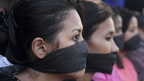 Photojournalists, with black bands around their mouth, participate in a protest against the gang rape of a photojournalist in Mumbai, in Gauhati, India, Saturday, Aug. 24, 2013.