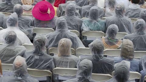 Attendees wear plastic rain ponchos as rain falls during the event.