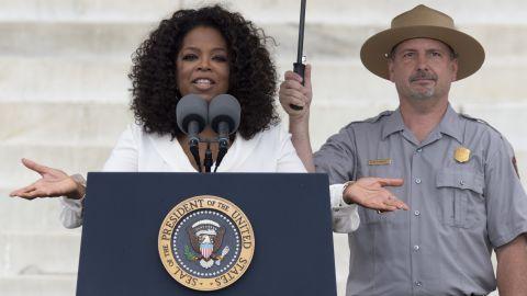 A park ranger holds an umbrella as Oprah Winfrey speaks during the event.