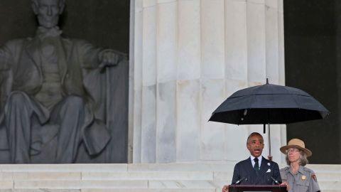 A light rain falls as the Rev. Al Sharpton addresses the crowd.