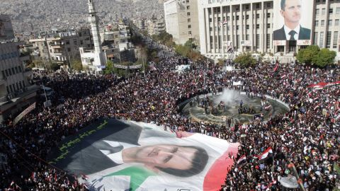 Syrian demonstrators carry a giant portrait of al-Assad in Damascus on November 28, 2011. Protesters waved Syrian flags and chanted nationalist songs in a demonstration against the Arab League's decision to impose crippling sanctions on the Assad regime.