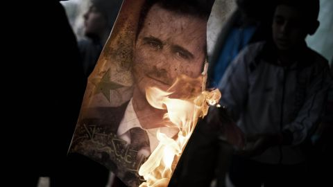 A member of the Free Syrian Army holds a burning portrait of al-Assad near the flashpoint city Homs on January 25, 2012.