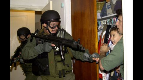 Elian Gonzalez, then 6, cowers in the arms of Donato Dalrymple on April 22, 2000, as federal officers charge in to take custody of the boy.