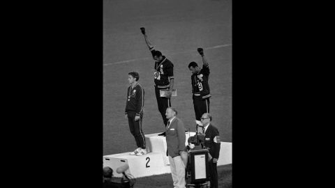 """American athletes Tommie Smith, center, and John Carlos raise their fists and hang their heads while the U.S. national anthem plays during their medal ceremony at the 1968 Summer Olympics in Mexico City. Their black power salute became front page news around the world as a symbol of the struggle for civil rights. To their left stood Australian Peter Norman, who <a href=""""http://www.cnn.com/2012/08/21/world/asia/australia-norman-olympic-apology/index.html"""">expressed his support</a> by wearing an Olympic Project for Human Rights badge."""
