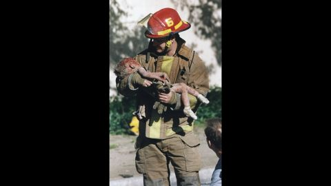 """Aspiring photojournalist Charles Porter was working near the Alfred P. Murrah Federal Building in Oklahoma City in 1995 when """"there was just a huge, huge explosion."""" He rushed to the scene and saw firefighter Chris Fields emerge from the rubble holding a dying infant, 1-year-old Baylee Almon. Porter's Pulitzer Prize-winning photograph of the moment became a symbol of the Oklahoma City bombing, which claimed 168 lives."""
