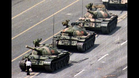 """Following a crackdown that resulted in the deaths of hundreds of student demonstrators in Beijing, a lone Chinese protester steps in front of People's Liberation Army tanks in Tiananmen Squarein 1989. At least five photographers captured the event, which became a symbol of defiance in the face of oppression. Charlie Cole, working for Newsweek, won a World Press Photo Award for his version of the image. The identity and fate of the """"Tank Man"""" remains unclear."""