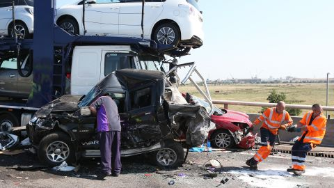 Vehicle recovery workers try to move a vehicle on the scene.