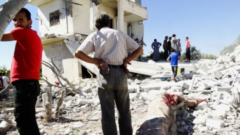 Men gather on the remains of a destroyed building after reported air strikes by Syrian government forces in the rebel-held northwestern Syrian province of Idlib on September 5, 2013. The Syrian Observatory for Human Rights watchdog said Syrian war planes bombed rebel held areas in Idlib, Aleppo, Hama and Lattakia.  AFP PHOTO / ABU AMAR AL-TAFTANAZ        (Photo credit should read ABU AMAR AL-TAFTANAZ/AFP/Getty Images)
