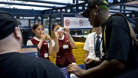 Airport staff take pictures of the former NBA star at a check-in counter in Beijing in September 2013.