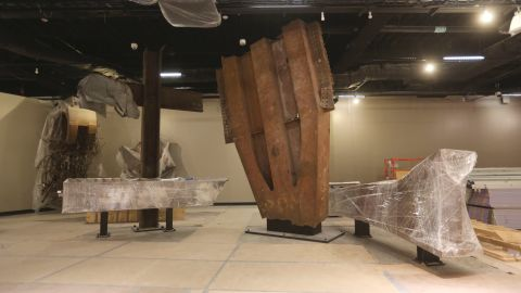 """The """"Cross,"""" made of intersecting steel beams found in the rubble of 6 World Trade Center, and a fragment of a trident column, center, one of 84 that formed the exterior structure of each tower, are prepared for display."""