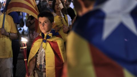 People wrapped in 'Estelada' Catalan independence flags march during a rally for independence in Barcelona on September 10.
