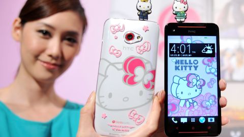 """A model displays Taiwan electronics giant HTC's new smartphone """"HTC Butterfly S Hello Kitty"""" with accessories during a press conference in Taipei on September 2, 2013."""
