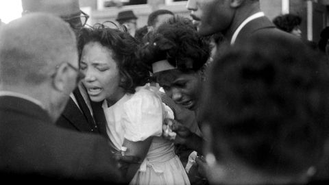 """Mourners embrace at the funeral. In his eulogy, Dr. King said, """"These children -- unoffending, innocent and beautiful -- were the victims of one of the most vicious and tragic crimes ever perpetrated against humanity."""""""