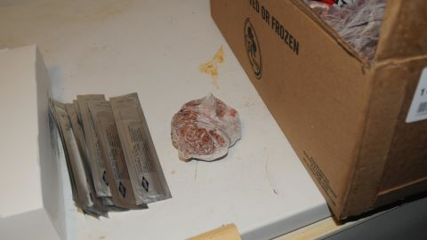 Disposable scalpels are found next to raw chicken.
