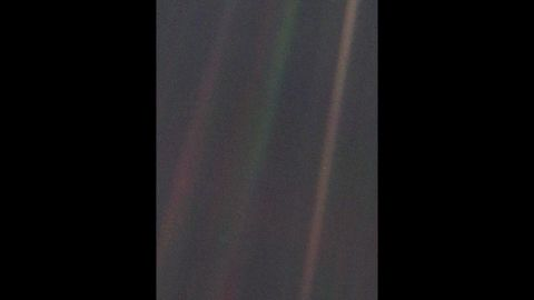 """This image of Earth, dubbed """"Pale Blue Dot,"""" is a part of the first """"portrait"""" of the solar system taken by Voyager 1. The spacecraft acquired a total of 60 frames for a mosaic of the solar system from a distance of more than 4 billion miles from Earth. Earth lies right in the center of one of the scattered light rays, which are the result of taking the image so close to the sun."""