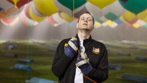 """Just like in the Disney movie """"Up,"""" Trappe is using 370 giant balloons filled with helium. He holds on to one of the many balloons that will be used to carry him across the Atlantic."""