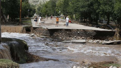 Water rushes where a bridge collapsed in a flash flood in Lyons, on September 13.