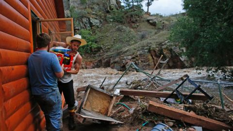 Chris Rodes helps Fred Rob salvage a friend's belongings after floods left homes and infrastructure in shambles in Lyons, Colorado, on September 13.