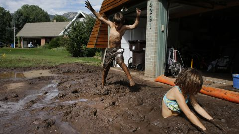 Eli and Noe Sura play in the mud around their Boulder, Colorado, home on September 14.