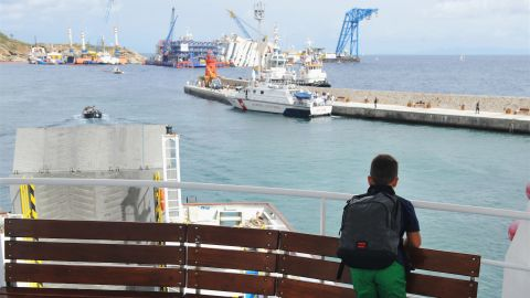 ISOLA DEL GIGLIO, ITALY - SEPTEMBER 15: A child looks out at the stricken Costa Concordia, which is prepared for the parbuckling project to upright the ship, on September 15, 2013 in Isola del Giglio, Italy. The Costa Concordia is reportedly due to be righted beginning on the morning of September 16, then, if the operation is successful, it will be towed away and scrapped. (Photo by Laura Lezza/Getty Images)
