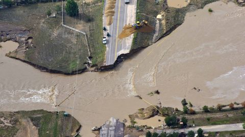 A road crew works on a stretch of highway washed away by flooding along the South Platte River near Greeley, Colorado, on Saturday, September 14.