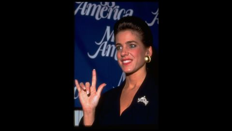 """Miss America 1995, Heather Whitestone, who is deaf, signs, """"I Love You"""" to reporters at a press conference."""