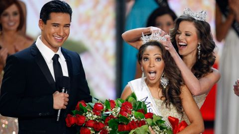 Host Mario Lopez, left, looks on as Miss America 2009 Katie Stam, right, crowns Caressa Cameron, formerly Miss Virginia, the new Miss America 2010.
