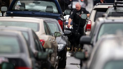 A police officer and police canine inspect vehicles in a parking lot outside the Washington Navy Yard.