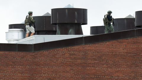 """Police officers walk on a rooftop at the Washington Navy Yard after a <a href=""""http://www.cnn.com/2013/09/16/us/dc-navy-yard-gunshots/index.html"""">shooting rampage</a> in the nation's capital in September 2013. At least 12 people and suspect Aaron Alexis were killed, according to authorities."""