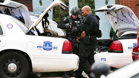 Two DC Metro Police officers put their gear up as they respond to a reported shooting at an entrance to the Washington Navy Yard September 16, 2013 in Washington, DC.