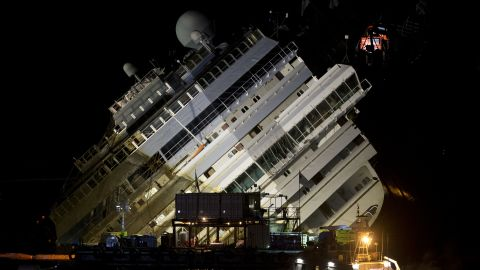 The Costa Concordia ship lies on its side on the Tuscan Island of Giglio, Italy, Monday, Sept. 16, 2013. Using a vast system of steel cables and pulleys, maritime engineers on Monday gingerly winched the massive hull of the Costa Concordia off the reef where the cruise ship capsized near an Italian island in January 2012. But progress in pulling the heavily listing luxury liner to an upright position w