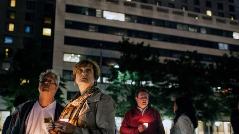 Gordon Morris, left, and wife Laura watch as flags are lowered to half-staff during the September 16 vigil at Freedom Plaza.