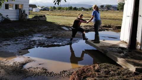 A woman steps over a puddle onto the foundation of a shed that was moved by floodwaters in Hygiene, Colorado, on Monday, September 16.